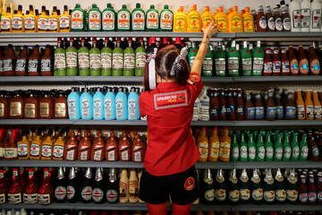 British artist Lucy Sparrow, 32, adjusts bottles of alcohol on shelves in her art installation supermarket in which everything is made of felt, in Los Angeles