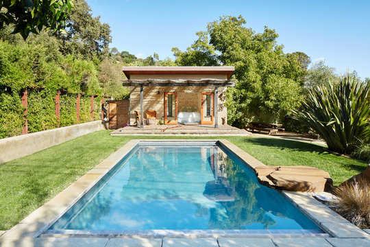 Pool and pool house in backyard of home in California