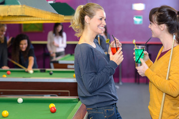 Ladies chatting with drinks in pool hall