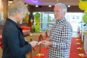 Man passing ticket to woman in lobby of theatre