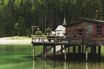 Beautiful wooden cabin on piles in a lake in the Dolomites, Italy