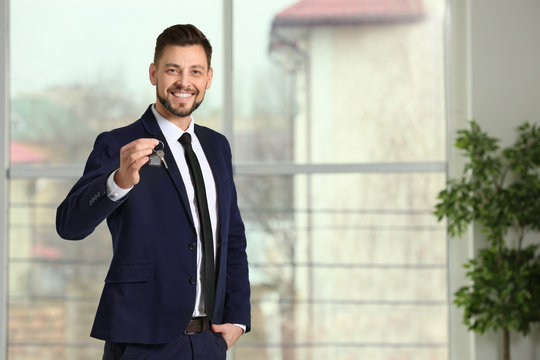 Real estate agent holding house key, indoors