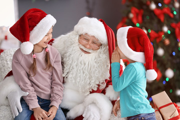 Little children sitting on authentic Santa Claus' knees indoors Wall mural