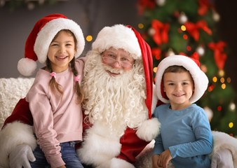 Little children sitting on authentic Santa Claus' knees indoors