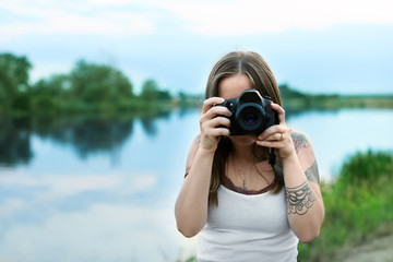 Young woman taking picture with professional camera outdoors