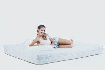 Young Smiling Woman Lying on Orthopedic Mattress