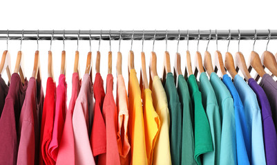 Rack with rainbow clothes on light background