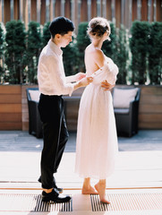A groom helping his bride with a dress
