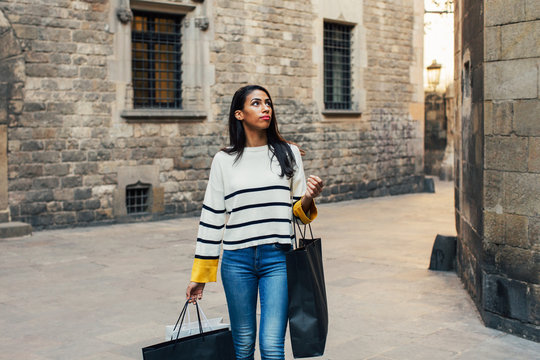 Stylish young woman walking with shopping bags on the street.