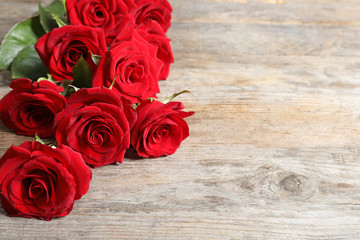 Beautiful red rose flowers on wooden background