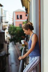 Woman having breakfast on the balcony, Granada, Spain.