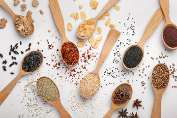Foto op Canvas Kruiden Composition with different aromatic spices in wooden spoons on white background