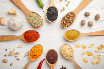 Flat lay composition with different aromatic spices in spoons on wooden background