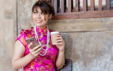 Attractive young woman wear cheongsam deep pink dress holding a cup coffee using smartphone. Festivities and Celebration concept