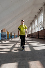 Young athlete walking along sports hall