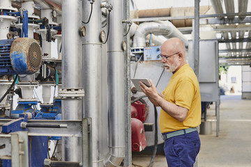 Senior Supervisor Using Digital Tablet By Machinery
