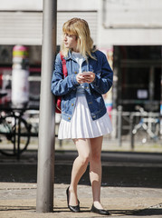 Young woman waiting to cross a street in Berlin, Germany.