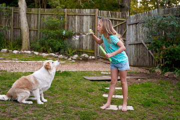 Girl blowing bubbles towards dog