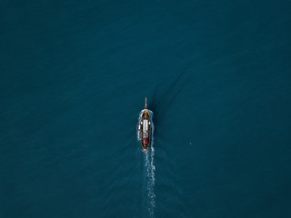 Aerial drone shot from above of boat floating in the arctic close to greenland