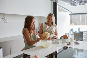 Mother and daughter mixing the dough and having fun cooking together