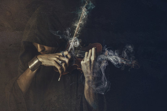 Dark phantom violin player, man performing a concert shrouded in smoke and fog