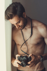 Sexy nude man, an amateur photographer, holding an slr camera