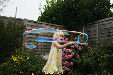 Little girl making big bubbles.