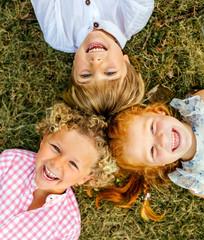 Three smiling children lying on the grass