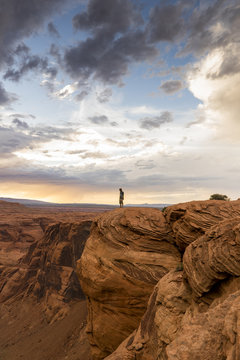 A man standing on the edge of Horse Shoe Bend