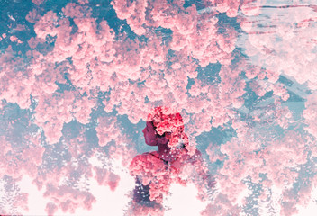 Woman standing in pool water covered in pink flowers