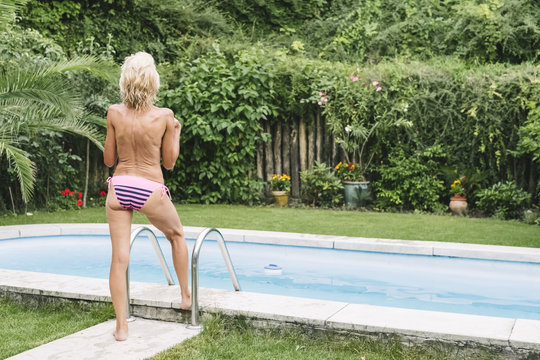 Senior woman topless in the home garden