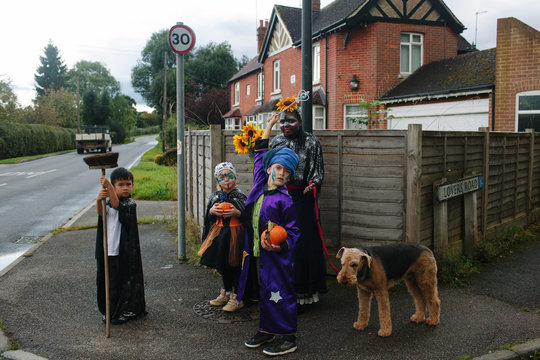 Four children and a dog go trick or treating.