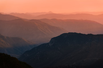 Sunset over mountain ranges of Sierra Nevada in California. Beautiful silhouette with multiple ridge layers and orange haze. Scenic landscape shot from Eleven Range Overlook in Sequoia National Park.