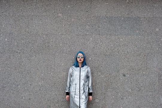 Girl wearing silver raincaot against a wall