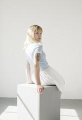 Portrait of a sunlit blonde woman sitting on a grey box.