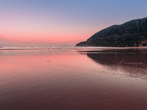 Landscape view of Neahkahnie Mountain from Manzanita Beach on the Pacific Coast of Northern Oregon. Pretty pink skies reflecting on the wet sand at sunrise. Residential area on the mountainside.