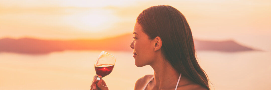 Asian woman drinking red wine glass watching sunset on travel europe holiday vacation - luxury lifestyle banner panorama landscape.