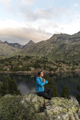 Female hiker meditating in an alpine scenery