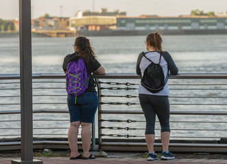 unknown sisters discuss life while watching the boats from the pier