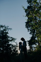 Silhouette of embracing mother and daughter among the trees
