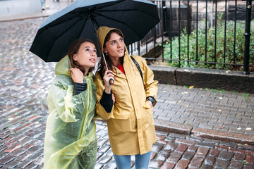Pretty young smiling and happy brunette woman tourists are looking the city under the rain
