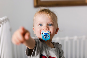 happy toddler in a crib with a pacifier after his nap