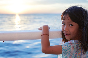 Asian little girl lying on the railing. On the cruise ship, the sea background