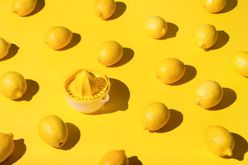 Lemons and juicer on yellow background
