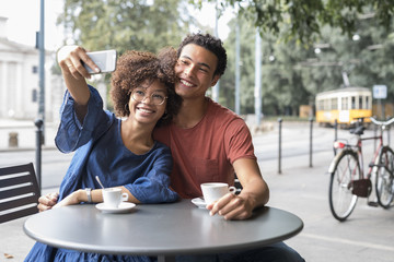 Happy black young couple sitting at cafe in the city  taking a selfie