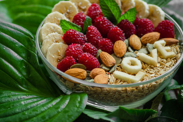Eating healthy breakfast bowl. The word LOVE in a plate with a healthy meal. Raspberry, Banana, Nuts. Vegetarian food concept