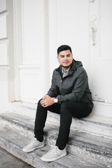 Young Hispanic - Latino Man Sitting in Front of White Building
