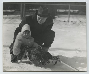 Young father in a hat plays with his baby daughter in the snow w