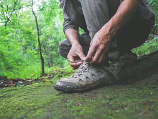 Hiker tying boot laces on green moss trail relax and enjoy in forest