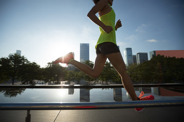 Healthy lifestyle woman runner running on sunrise city